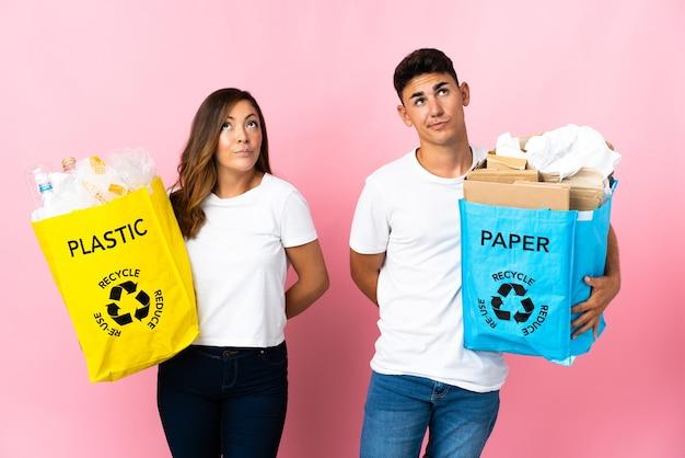 Giovani coppie che tengono un sacchetto pieno di plastica e carta sul rosa e alzando lo sguardo