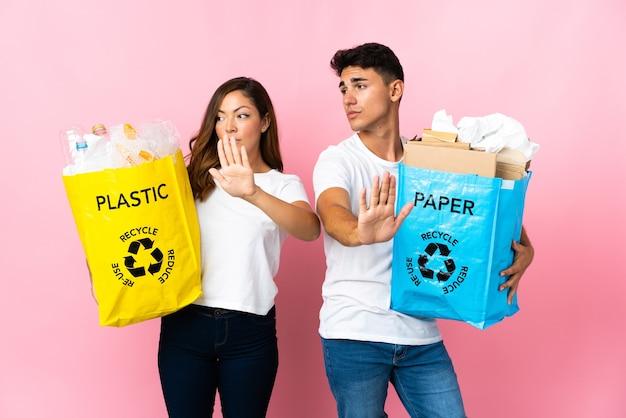 Giovani coppie che tengono un sacchetto pieno di plastica e carta sul rosa facendo gesto di arresto e deluso