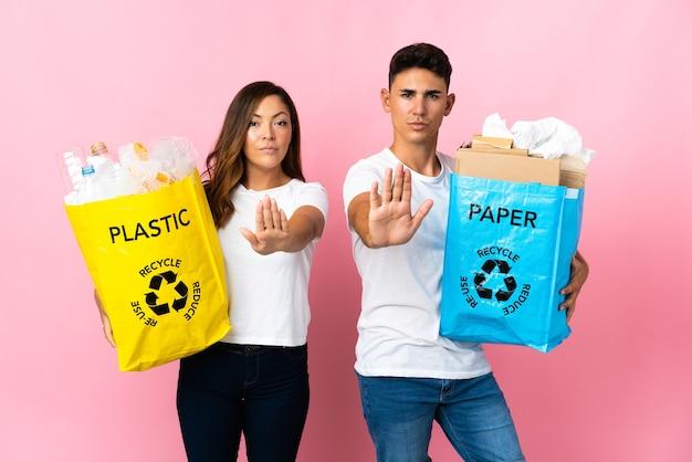Giovani coppie che tengono un sacchetto pieno di plastica e carta sul gesto di arresto di fabbricazione rosa