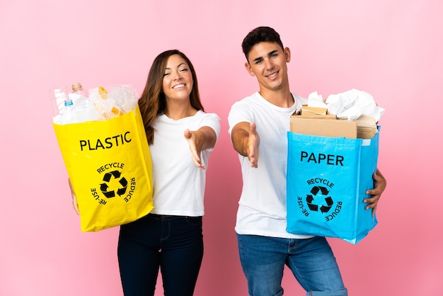 Giovani coppie che tengono un sacchetto pieno di plastica e carta sul rosa che agitano le mani per chiudere un buon affare