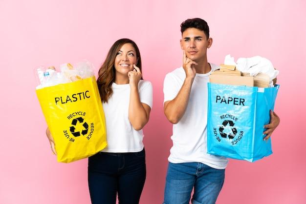 Giovani coppie che tengono un sacchetto pieno di plastica e carta sul rosa pensando un'idea mentre guarda in alto