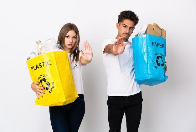 Giovani coppie che tengono un sacchetto pieno di plastica e carta su bianco che fa gesto di arresto