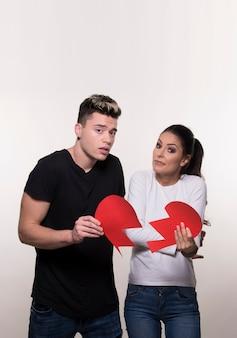 Giovane coppia che tiene metà del cuore isolato su sfondo bianco