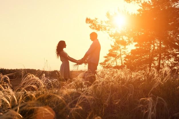 Giovani coppie che si tengono per mano nell'alba della natura