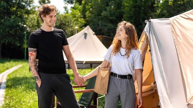 Giovani coppie che si tengono per mano vicino alla tenda al glamping. verde intorno
