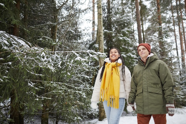 Giovani coppie che tengono le mani camminando all'aperto nella foresta e godersi la giornata invernale