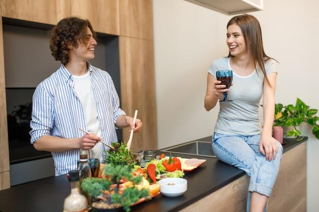 Coppia giovane tenendo il bicchiere di vino in cucina a casa
