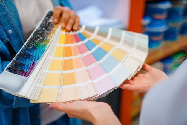 La giovane coppia tiene la tavolozza dei colori nel negozio di ferramenta.