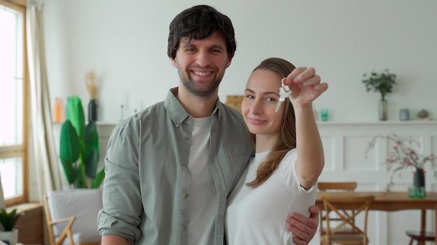 La giovane coppia tiene felicemente una chiave per la loro nuova casa