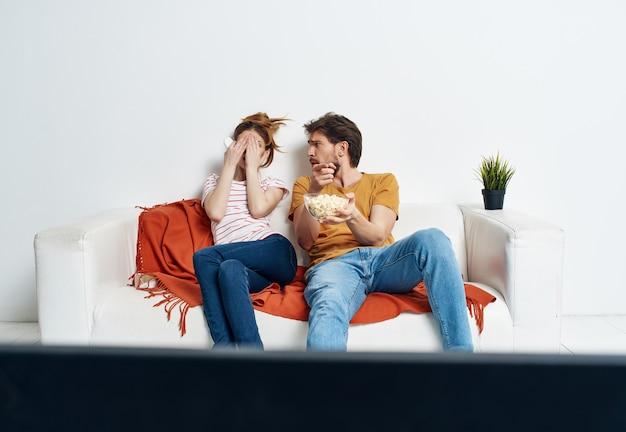 Giovane coppia a casa sul divano a guardare una vacanza al cinema