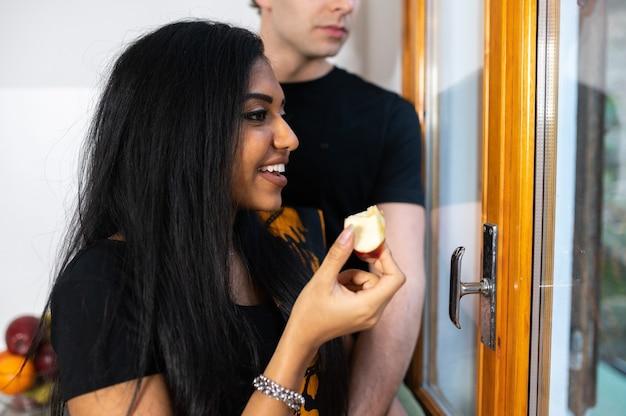 Coppia giovane a casa a mangiare la mela in cucina