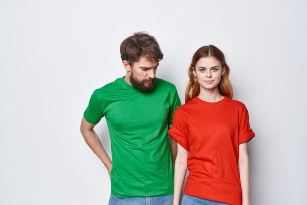 Una giovane coppia abbraccia amicizia magliette colorate famiglia sfondo chiaro