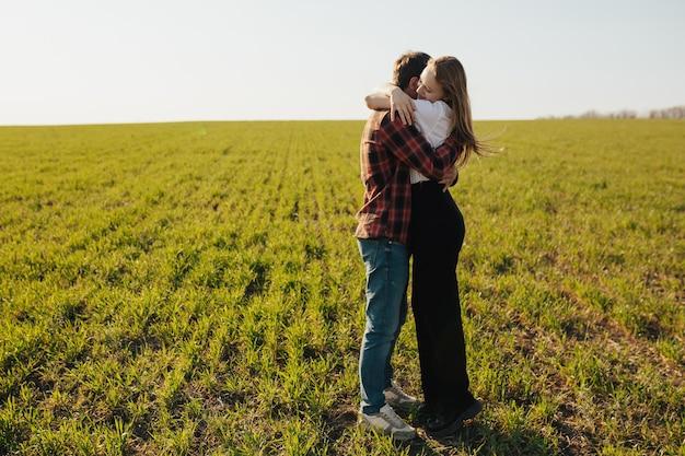 Giovani coppie che abbracciano in un campo di grano al giorno di primavera.