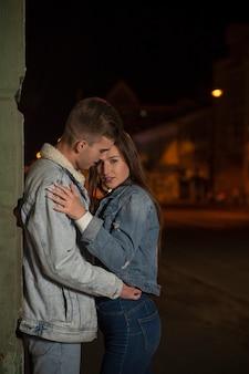 Abbracci di giovane coppia sullo sfondo della città di sera. bella giovane coppia innamorata. appuntamento romantico per strada.
