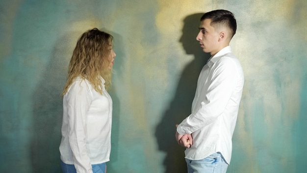 Coppia giovane marito e moglie litigano e si urlano in piedi vicino al muro, vista laterale.