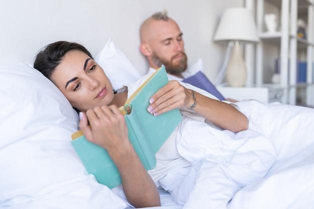 Coppia giovane marito con moglie a casa a letto a leggere libri in autunno inverno sera, l'uomo si è addormentato