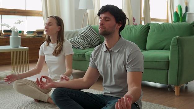 La giovane coppia sta facendo allenamento fitness a casa.