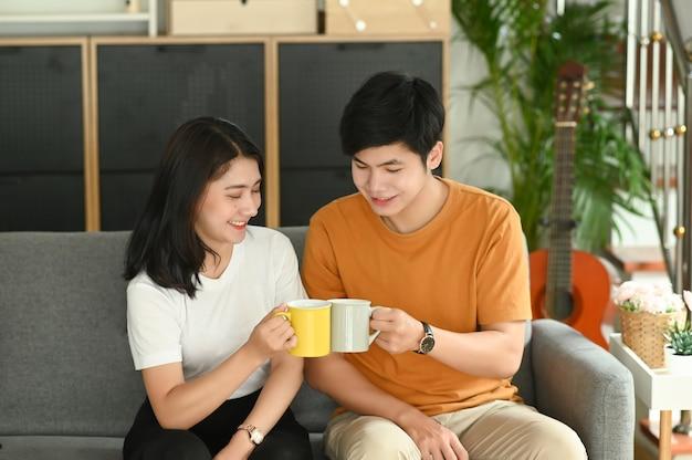 Una giovane coppia sta bevendo il caffè insieme sul divano la mattina a casa