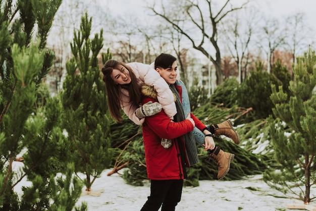 Una giovane coppia sta scherzando, divertendosi in inverno contro il mercatino degli alberi di natale