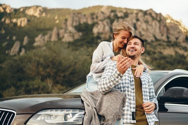 La giovane coppia è in viaggio romantico in montagna in auto