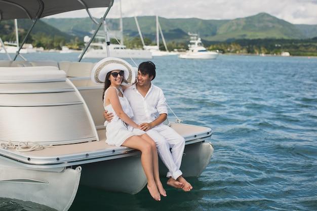 La giovane coppia sta navigando su uno yacht nell'oceano indiano. l'uomo e la donna si siedono sul bordo dello yacht