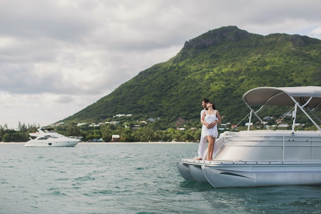 La giovane coppia sta viaggiando su uno yacht nell'oceano indiano. a prua della barca, una famiglia amorevole si abbraccia