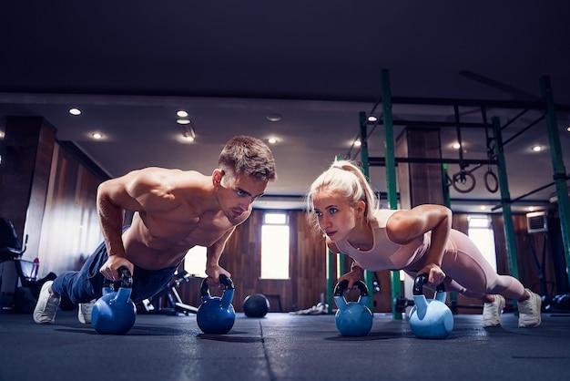 La giovane coppia sta lavorando in palestra. donna attraente e bell'uomo muscoloso si stanno allenando nella moderna palestra. fare plank con il kettlebell. push-up sui pesi.