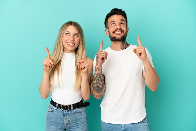 Coppia giovane su sfondo blu isolato rivolto verso l'alto con il dito indice una grande idea