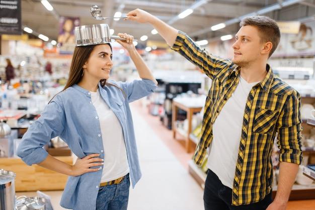 La giovane coppia scherza con il mestolo e la padella nel negozio di casalinghi. uomo e donna che acquistano beni per la casa nel mercato, famiglia nel negozio di articoli da cucina