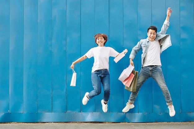 Giovani coppie che saltano con i sacchetti della spesa