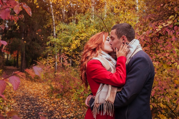 Baci di giovane coppia nella foresta autunnale tra alberi colorati
