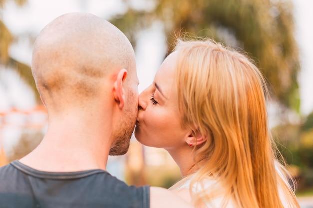 Giovane coppia baci sulla guancia. la donna bacia il suo amante.