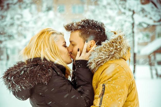Giovane coppia che si bacia per strada nella neve