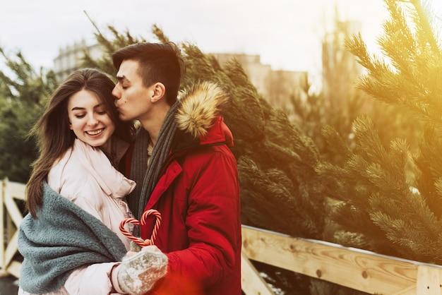 Una giovane coppia che si bacia in inverno sullo sfondo del mercato degli alberi di natale in città
