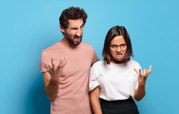 Giovani coppie che guardano wtf urlando arrabbiato, infastidito e frustrato