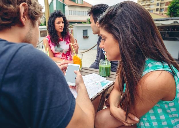 Giovane coppia in cerca di smartphone seduti intorno al tavolo con i loro amici in una giornata estiva all'aperto