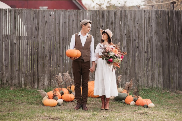 Una giovane coppia si guarda teneramente. un uomo sta con una zucca in mano e una ragazza con un bouquet.