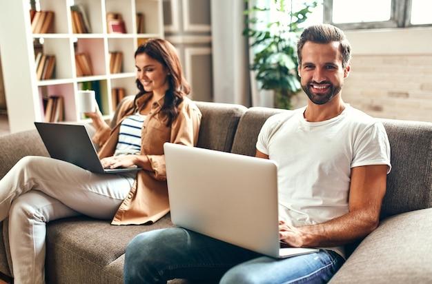 La giovane coppia innamorata è seduta sul divano con i computer portatili nel soggiorno di casa. acquisti online, lavoro da casa, freelance.