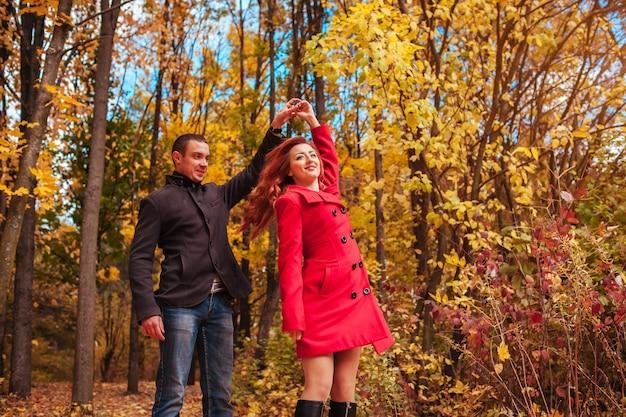 Giovane coppia innamorata che balla nella foresta autunnale tra alberi colorati