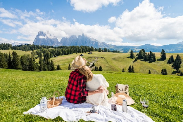 Giovane coppia innamorata facendo picnic visitando le dolomiti delle alpi