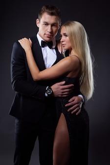 Una giovane coppia innamorata vestita con abiti classici in un tenero abbraccio.
