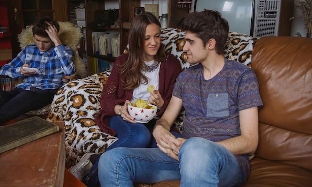 Giovane coppia innamorata che mangia patatine fritte seduti su un divano e il loro amico che guarda lo smartphone in una giornata noiosa a casa. concetto di tempo libero dell'adolescente.