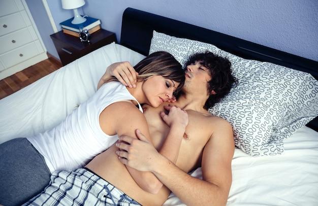 Giovane coppia innamorata che si rilassa insieme sdraiata su un letto con la donna che riposa sul petto dell'uomo. amore e concetto di relazioni di coppia.