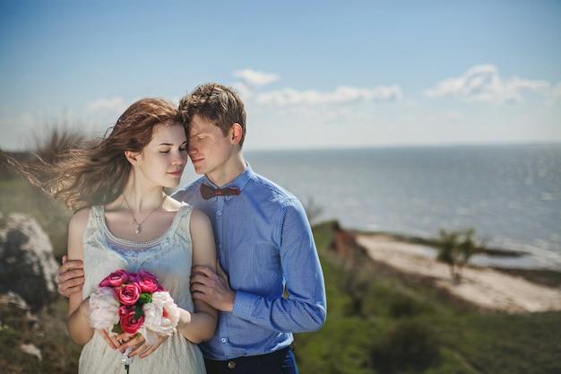 Una giovane coppia innamorata che si abbraccia si trova su una scogliera a picco sul mare in estate con un bouquet in mano