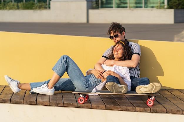 Giovani coppie innamorate si godono il tramonto seduti abbracciati su longboard uomo e donna alla moda che si rilassano all'aperto