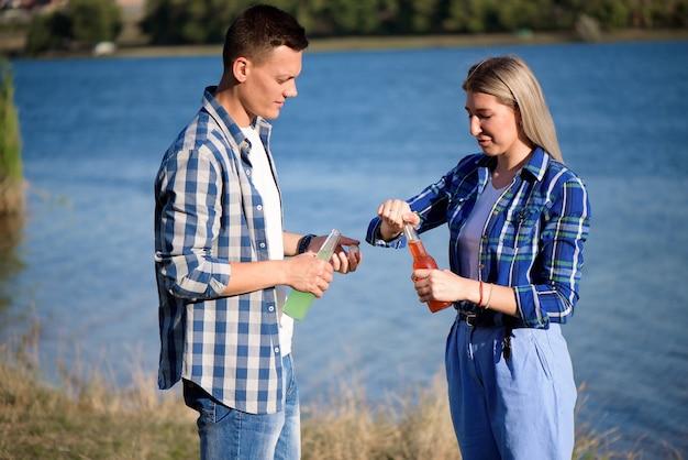Giovani coppie nell'amore che gode del cocktail sulla spiaggia.