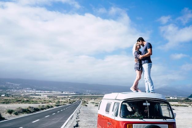 Giovane coppia innamorata che si gode il viaggio su un furgone vintage in piedi sul tetto e si abbraccia con un bacio - giovani in attività ricreative e trasporti all'aperto