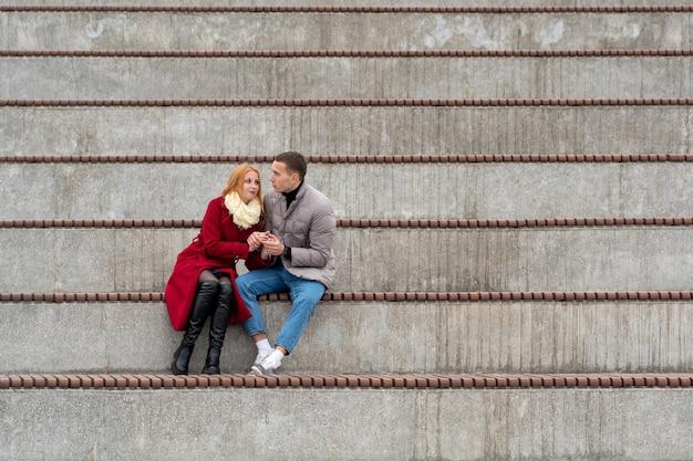 Giovane coppia innamorata, un ragazzo e una ragazza sono seduti insieme su una tribuna vuota