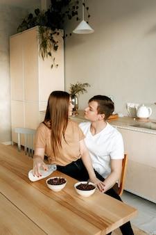 Una giovane coppia innamorata fa colazione insieme a casa in cucina. uomo e donna che mangiano cereale con latte per la prima colazione.