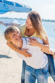 Giovani coppie nell'amore divertendosi e saltando sulla spiaggia